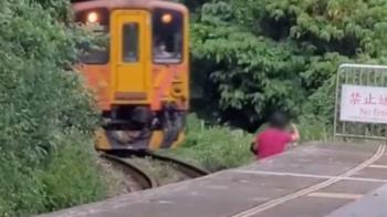 差點輾過!婦站鐵軌架腳架自拍 火車狂按喇叭急煞車