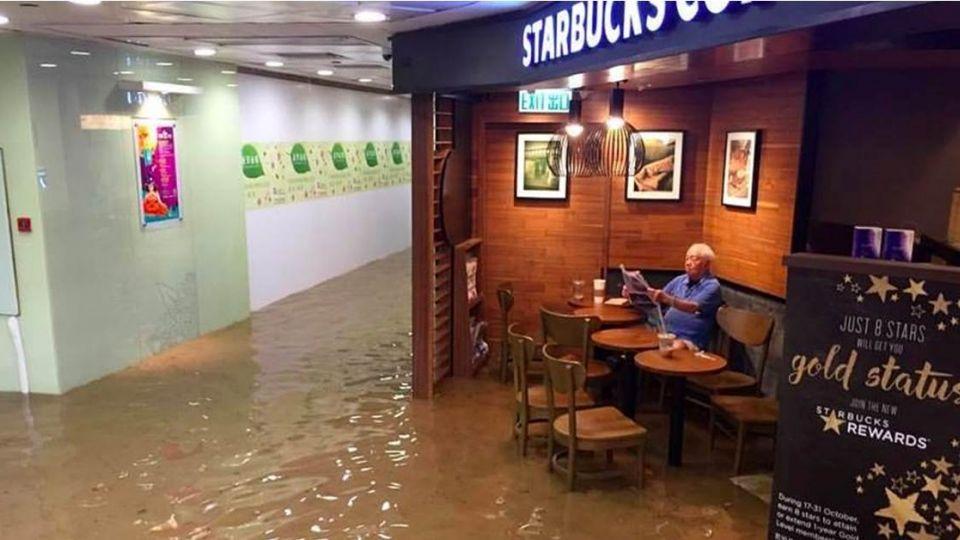包子嬸新對手!超淡定「星巴克老伯」淹水照樣看報喝咖啡