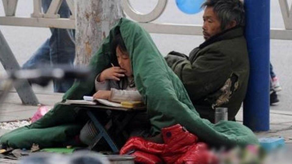 寒風中披棉被陪父親上街乞討 6歲女童仍不忘勤奮學習