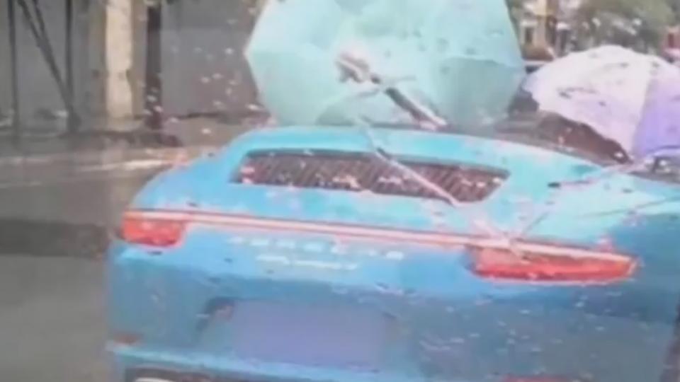 有錢任性? 傾盆大雨 駕駛撐傘開敞篷跑車