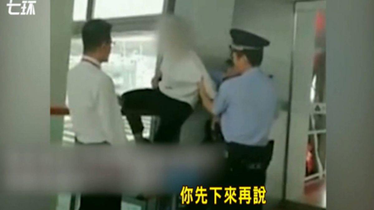陸女遲到…不滿登機被拒!爬欄杆嗆警:我摔你賠嗎?